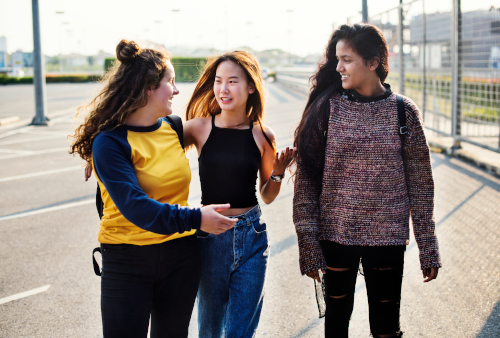 Three young women casually walking and talking, having fun