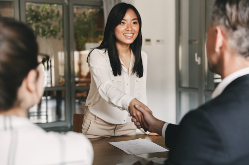 College applicant shakes hands with two interviewers at a desk