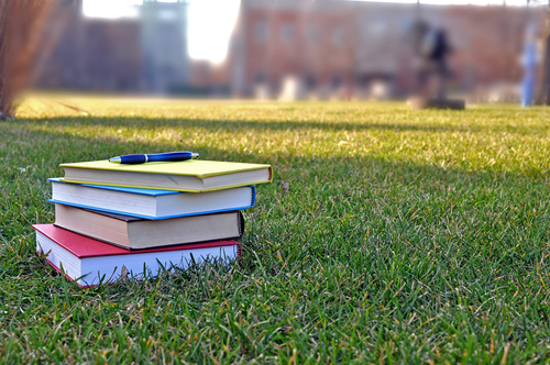 A stack of books on the grass in a college campus courtyard
