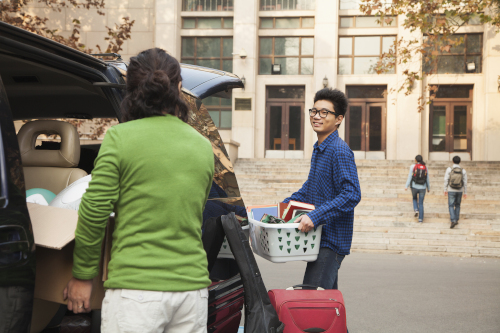A young man and his parents unload bedding and books from the car, dropping off at college