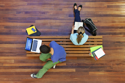 Overhead view of two students studying on a bench indoors