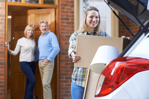 Young woman loading her car to leave to college as her parents look on
